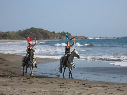 Equestrians are thrilled from the ride in the surf. / Pferdefreunde sind begeistert davon in den Wellen zu reiten.